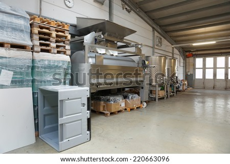 Non-functioning winemaking equipment in a hangar - stock photo
