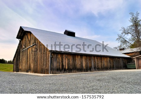 Non-residential  wooden warehouse in countryside under clear blue sky - stock photo