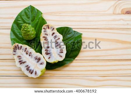 Noni fruit on wooden background - stock photo