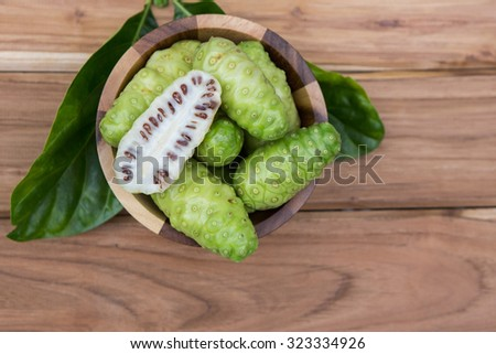 Noni green rests on a wooden floor. - stock photo