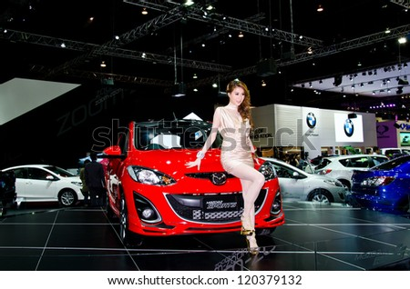 NONTHABURI - NOVEMBER 28: Mazda 2 Sport car with unidentified model on display at The 29th Thailand International Motor Expo on November 28, 2012 in Nonthaburi, Thailand.