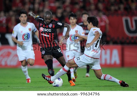 NONTHABURI THAILAND-March17:Christian Kouakou (red) of SCG Muangthong Utd.in action during Thai Premier League between BEC Tero F.C.and SCG MuangThong utd. on March17,2012 in Nonthaburi,Thailand - stock photo