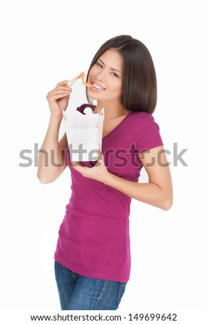 Noodle box. Beautiful mixed race woman eating noodles from food container while isolated on white - stock photo