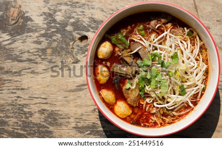 Noodle Khao soi Nam Ngieow , Thai food on wood background  - stock photo