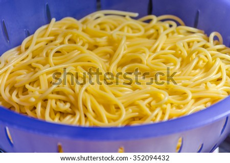 Noodles in a colander under cold water after the scare. - stock photo