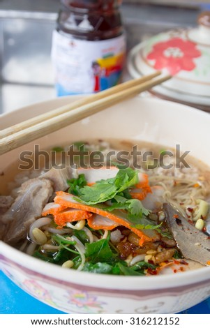 Noodles spicy in bowl and chopsticks. - stock photo