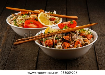 Noodles with seafood on wooden table - stock photo