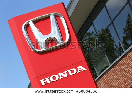 NOORDWIJK, THE NETHERLANDS - July 3, 2016: Honda dealership sign in front of the showroom. Honda is the second-largest Japanese automobile manufacturer. - stock photo