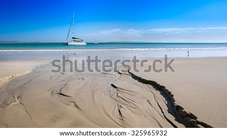 Noosa Heads Beautiful Tropical Beach With A Glassy Stream Eroding The Sand And Flowing Towards Two Sailboats On A Sunny Day During Summer, Little Cove, Sunshine Coast, Queensland, Australia - stock photo