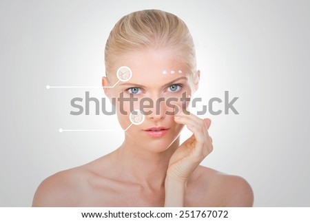 nordic girl with indicators on her face checking the results of her cream on grey background - stock photo