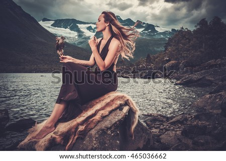 Nordic goddess in ritual garment with hawk near wild mountain lake in Innerdalen valley, Norway.