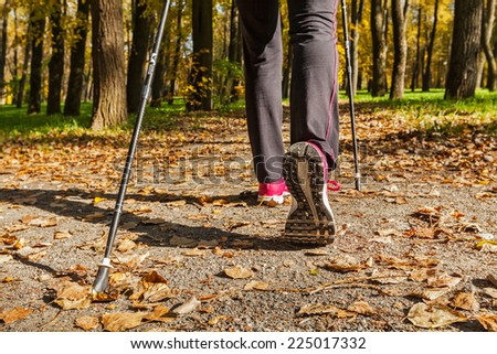 Nordic walking: adventure and exercising concept - woman hiking, legs and nordic walking poles in autumn nature - stock photo