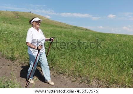 Nordic Walking - elderly woman is hiking   - stock photo