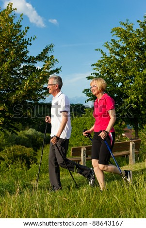 Nordic Walking - Happy mature or senior couple doing sports in summer outdoors - stock photo