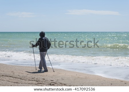 Nordic walking. Man hiking on the beach in Yevpatoriya (Evpatoria), Crimea. Active and healthy lifestyle.