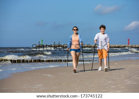 Nordic walking - young people working out on beach - stock photo