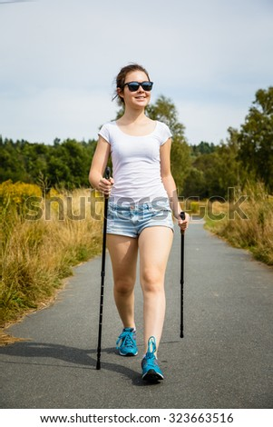 Nordic walking - young woman working out in park  - stock photo