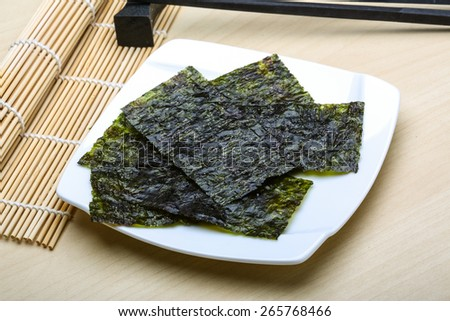 Nori sheets with sticks on the wood background - stock photo