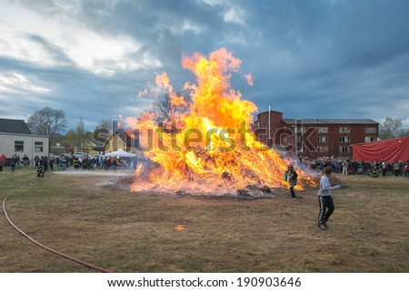NORRTALJE - APR, 30, 2014: The traditional Valborg fire at Haverodal with two kids heating mashmallows at April 30, 2014, Norrtalje, Sweden. Tradition in the Nordic countries to welcome the spring. - stock photo