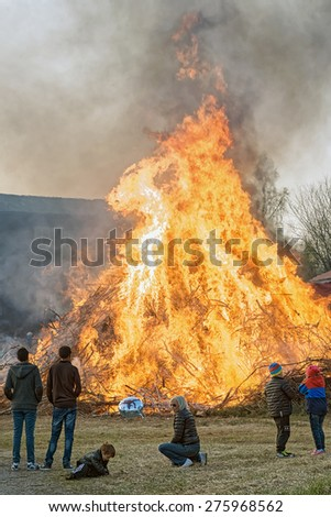 NORRTALJE - APR, 30, 2015: The traditional Walpurgis (Valborg) fire at Haverodal with peolple warming at April 30, 2015, Norrtalje, Sweden. Tradition in the Nordic countries to welcome the spring.