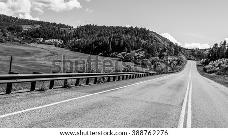 North american endless asphalt mountain road in beautiful sunny autumn weather somewhere in the USA, black and white image - stock photo