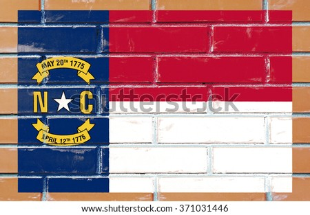 North Carolina state flag of America on brick wall - stock photo