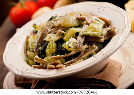 North Italian Regional pasta dish called pizzoccheri on wooden table - stock photo
