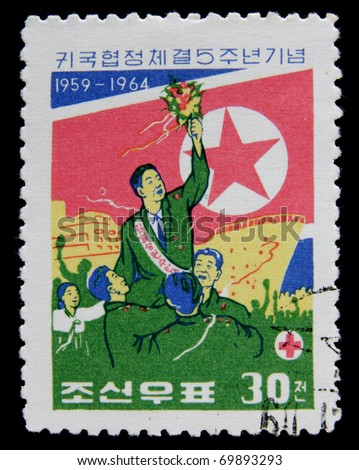 NORTH KOREA - CIRCA 1964: A post stamp printed in North Korea shows korean workers against of a ship , circa 1964