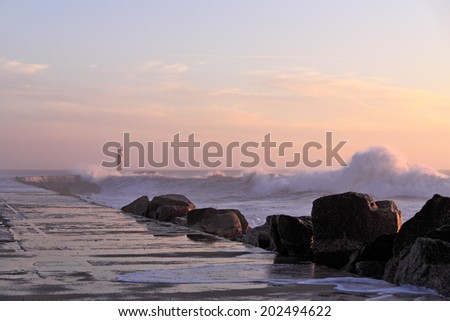 North of Portugal seascape in autumn seeing waves against a pier and lighthouse. Ave river mouth, Vila do Conde. - stock photo