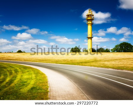 North sea landscape with road and yellow lighthouse on the dike. Friesland, Germany travel destination - stock photo