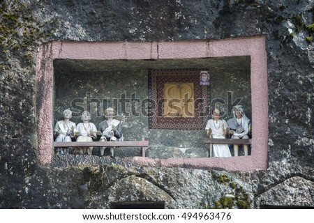North Toraja, Indonesia-Aug 28, 2016:The door of the burial site with coffins placed in caves carved into the rock, decorated with the wooden statues and images of the dead persons in Lo'Ko'Mata.