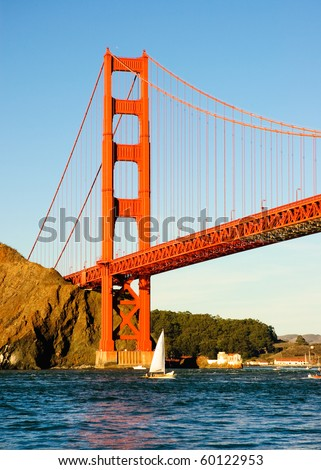 North tower of the Golden Gate Bridge from the cabbage patch as a boat goes under it at sunset - stock photo