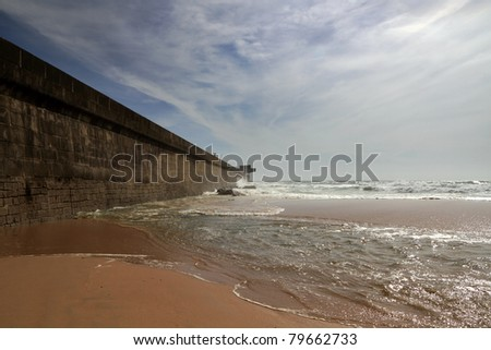 North wall of Leixoes Harbor and part of the beach of Leca da Palmeira in the north of Portugal, near Porto - stock photo