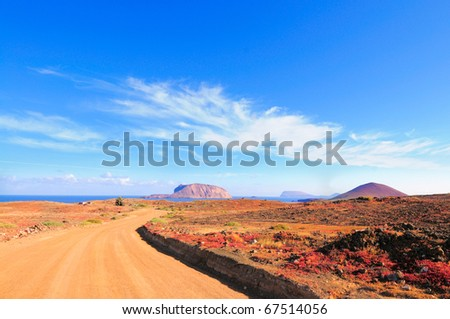 North-Western edge of Island Graciosa with an ancient volcano on the right and Island Montana Clara across the water. There is an ongoing construction of roads from the harbor. Canary islands, Spain - stock photo