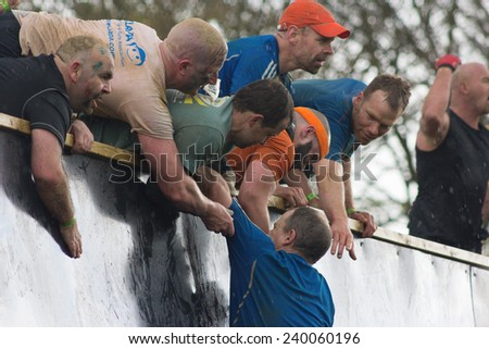"""NORTHAMPTONSHIRE/UK - May 4, 2013:  Tough Mudders who conquered """"Everest"""", an obstacle on the course, lend support to others  at the annual Tough Mudder extreme sports. - stock photo"""