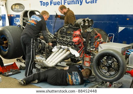 NORTHAMPTONSHIRE, UK - OCT 29: Mechanics working on a top fuel funny car at the Flame and Thunder drag-racing event on Oct 29, 2011 at Santa Pod Raceway in Northamptonshire, UK - stock photo