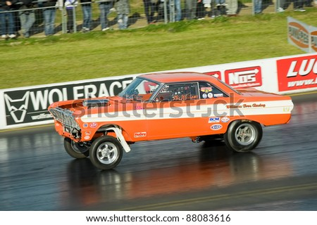 NORTHAMPTONSHIRE, UK - OCT 29: Pro modified Ford Falcon hotrod drag racing at the Flame and Thunder event on Oct 29, 2011 at Santa Pod Raceway in Northamptonshire, UK - stock photo