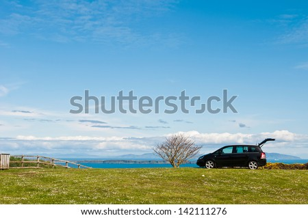 NORTHERN IRELAND - MAY 9: unidentified black suv at the countryside where a family decided to enjoy a holiday outdoors in Northern Ireland, United Kingdom on May 9, 2012. - stock photo