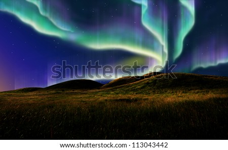 northern light on the silent field before sun rise. - stock photo
