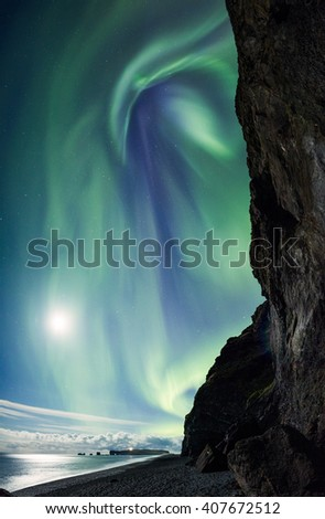 Northern Lights above an Icelandic beach Reynisfjara in Vik - stock photo
