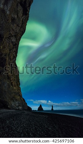 Northern Lights above Vik beach and cliffs in Iceland