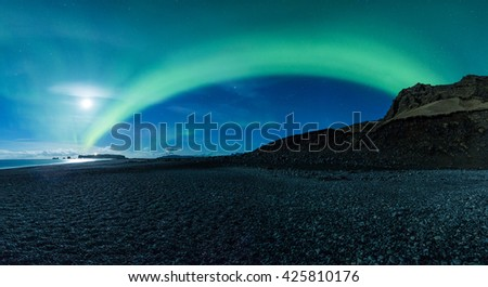 Northern Lights arc above a black sand beach - stock photo