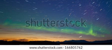 Northern lights  Aurora borealis and shooting star meteor at midnight in summer over northern horizon of Lake Laberge  Yukon Territory  Canada  at early dawn - stock photo