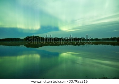 Northern lights (Aurora Borealis) glowing in the night sky over a beautiful lake in Finland. Vibrant colors on the sky and symmetric reflections on the still water of the lake. - stock photo