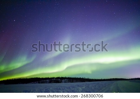 Northern lights aurora borealis in the night sky over beautiful frozen lake landscape - stock photo
