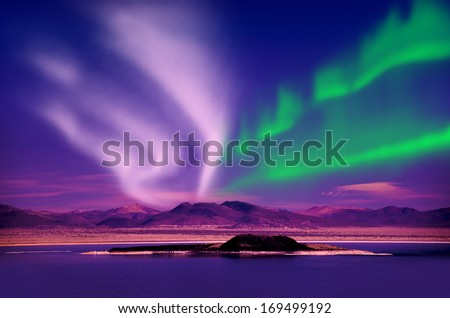 Northern lights aurora borealis in the night sky over beautiful lake landscape - stock photo