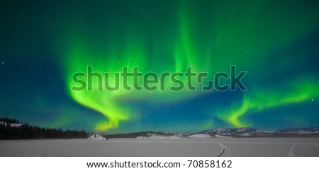 Northern Lights (Aurora borealis) over moon lit snowscape of frozen lake and forested hills. - stock photo