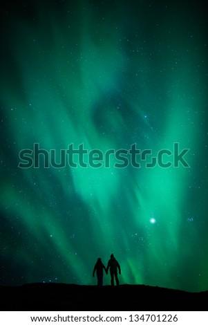 Northern Lights (Aurora Borealis) over romantic couple on honeymoon in Iceland - stock photo