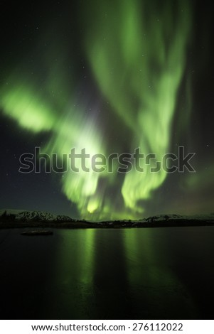 Northern lights blazing over lake Thingvellir in Iceland in the winter of 2015 - stock photo