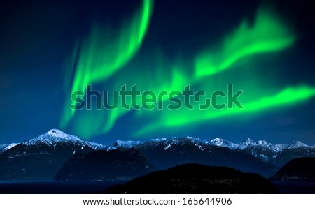 Northern Lights over mountains and lake - stock photo